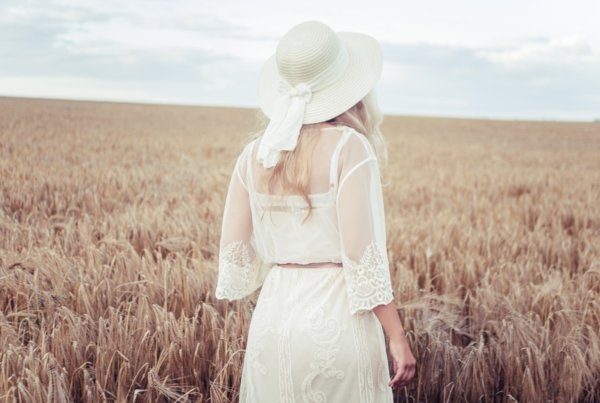 woman in white dress wearing white sun hat standing on brown grass field during daytime